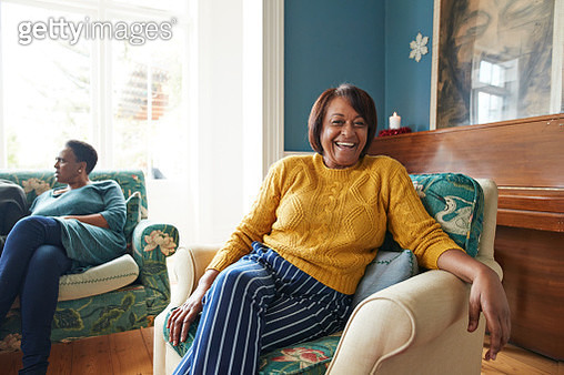 Portrait of cheerful mature woman sitting on armchair at home during Christmas festival - gettyimageskorea