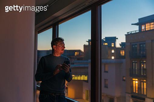 Man looking out of window - dusk - gettyimageskorea