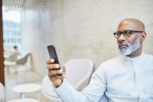 Portrait of bald mature businessman with cell phone - gettyimageskorea