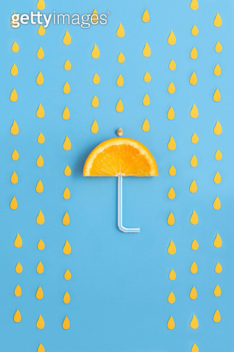 Orange slice arranged in umbrella shape or form on blue background. Protection of health and well being with goodness of oranges. - gettyimageskorea