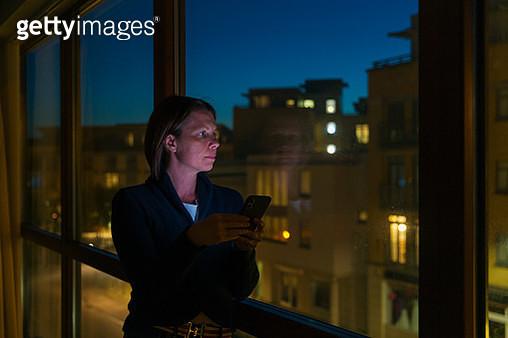 Woman looking out of window - dusk - gettyimageskorea