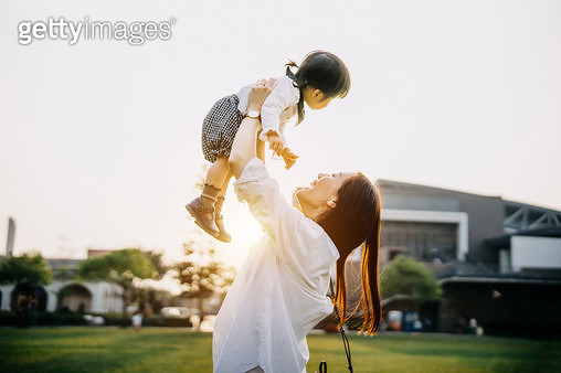 Joyful mother enjoying happy family time with daughter and lifting her in the air in the park - gettyimageskorea