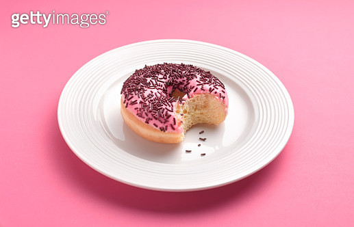 Pink doughnut on white plate on pink background with bite removed - gettyimageskorea