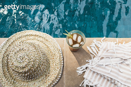 Cold summer poolside drink with ice, straw hat and towel near swimming pool - gettyimageskorea