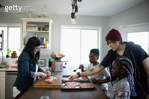 Family making homemade pizzas in kitchen - gettyimageskorea
