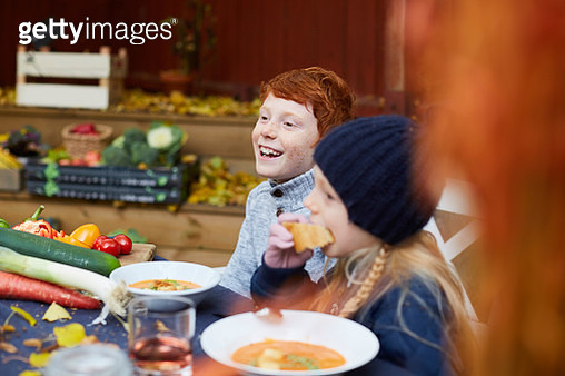 Happy male and female siblings sitting for meal at table - gettyimageskorea