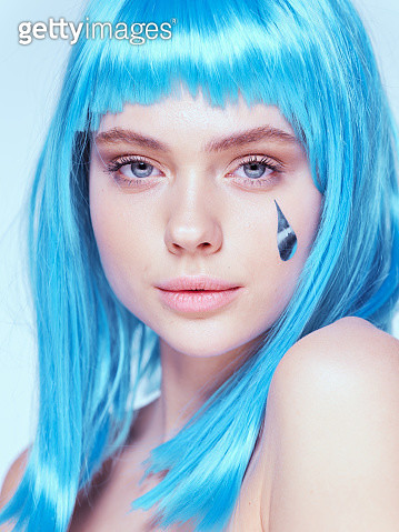 A young girl without clothes with blue hair and a tear on her cheek. - gettyimageskorea