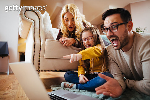 Family using laptop at home and watching movie - gettyimageskorea