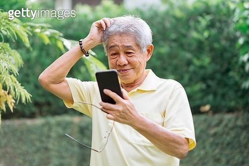 Portrait of Senior Chinese Man Using Smartphone - gettyimageskorea