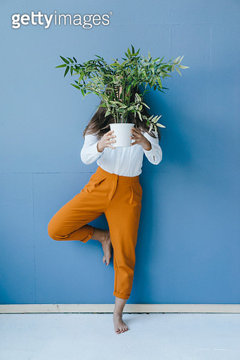 Pretty young woman holding potted plant in front of her face - gettyimageskorea