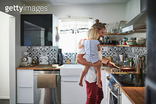 Mid adult father carrying daughter while cooking food in kitchen - gettyimageskorea