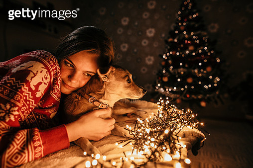 Young woman next to the Christmas tree and hugs her dog on a New year's eve - gettyimageskorea