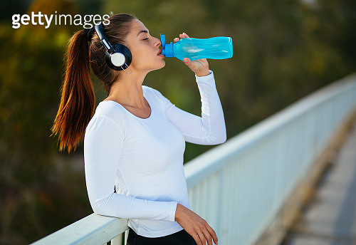 Photo of young beautiful woman drinking water and listening to music - gettyimageskorea