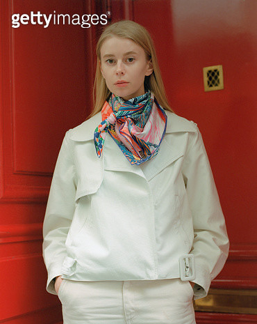 Portrait of beautiful young woman with long blond hair wearing white leather jacket colorful silk scarf and white jeans standing near red door. - gettyimageskorea