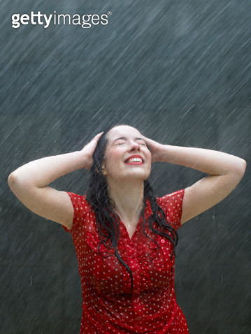 Young woman leaning back in rain, hands on head, eyes closed - gettyimageskorea