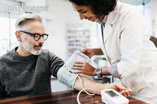 A pharmacist measuring a mature man's blood pressure using specialist equipment. - gettyimageskorea