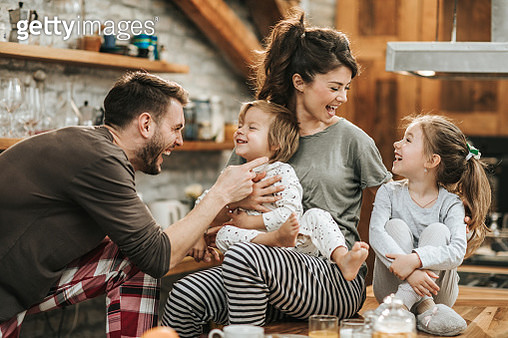 Happy parents playing with their small kids during breakfast time in the kitchen. - gettyimageskorea