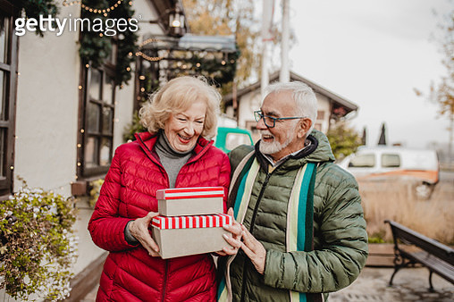 Loving senior couple enjoying outdoors and holding Christmas presents - gettyimageskorea