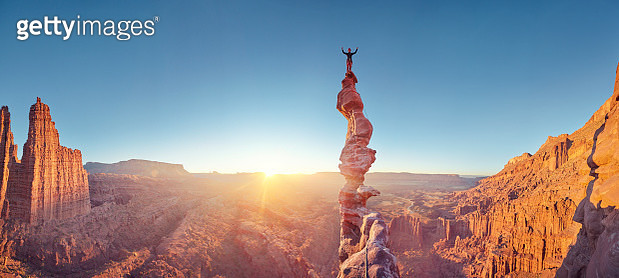 Rock climber celebrating on top of summit of climb at sunset, Ancient Art, Moab, USA - gettyimageskorea