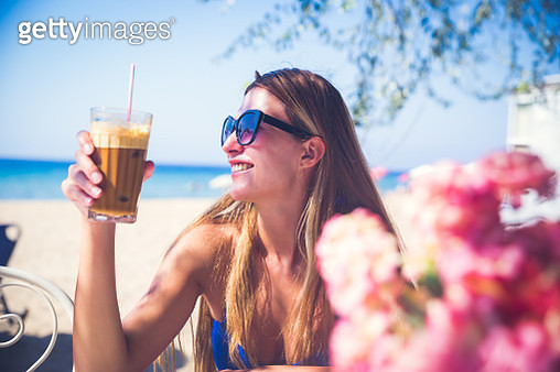 Young Woman relaxing with frappe coffee relaxing on sea vacation - gettyimageskorea