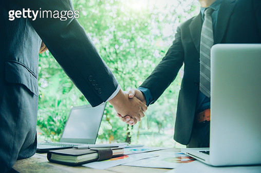 Midsection Of Businessmen Shaking Hands While Standing At Desk - gettyimageskorea