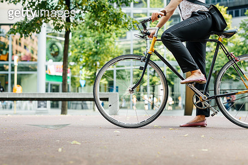Legs of a young businesswoman on a bicycle - gettyimageskorea