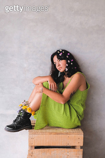 Sad young woman in a bright dress sitting on a box in flowers - gettyimageskorea