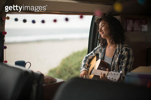 Young Asian woman sitting in her camper van playing a guitar - gettyimageskorea