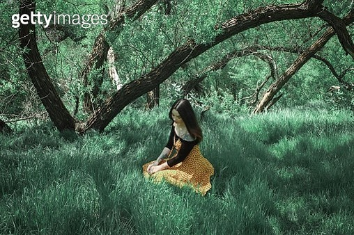 Young Woman Sitting On Grassy Field - gettyimageskorea