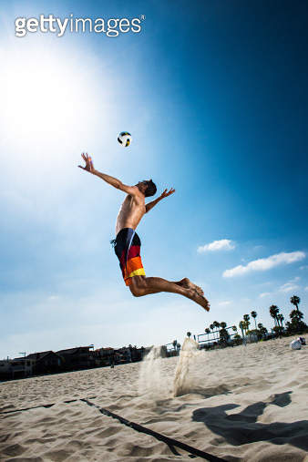 Male beach volleyball player jumping mid air to hit ball - gettyimageskorea
