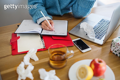 Midsection of sick mature woman sitting indoors in kitchen, working in home office. - gettyimageskorea