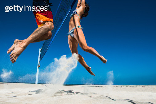 Two beach volleyball players blocking at net - gettyimageskorea