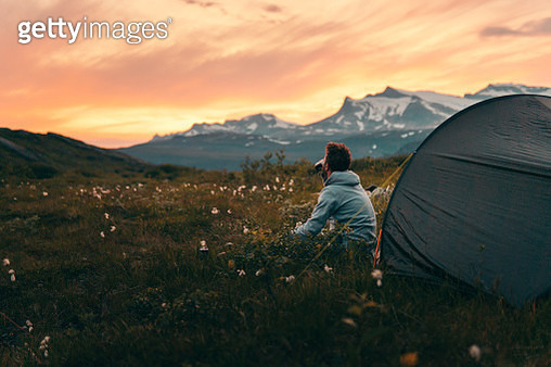 Tent on a mountain top during sunset, man looking on view - gettyimageskorea