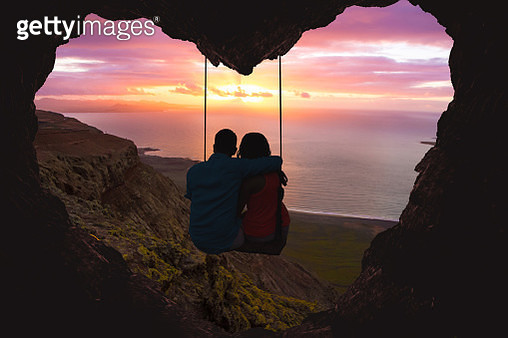 Couple on swing contemplating the sunset over the sea in a romantic view with heart shape. - gettyimageskorea