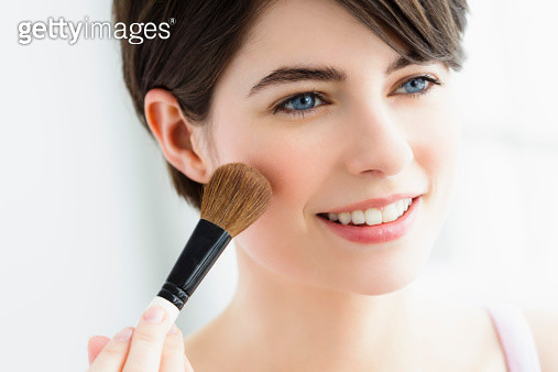 Germany, Bavaria, Munich, Young woman using blusher brush, close up - gettyimageskorea