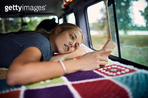 Young woman lying on blanket in an off-road vehicle using smartphone - gettyimageskorea