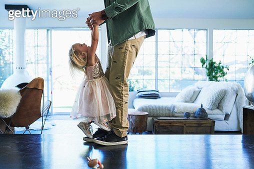 Daughter standing on feet of father dancing - gettyimageskorea