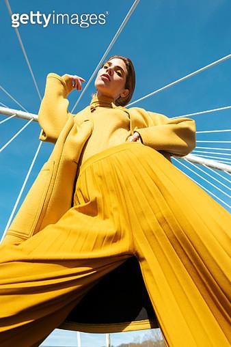 Stylish woman standing on modern architectural bridge - gettyimageskorea