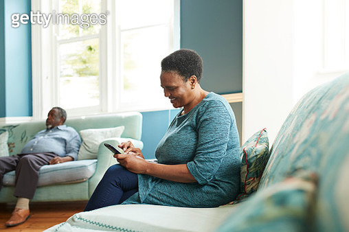 Smiling senior woman using smart phone while sitting on sofa at home - gettyimageskorea