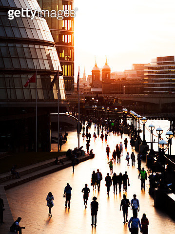 Tourists and commuters in London Riverbank against sunset sky - gettyimageskorea