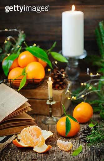 Fresh Tangerines with leaves and books on wooden table. - gettyimageskorea