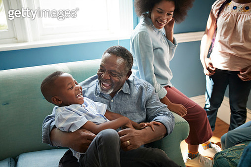 High angle view of happy man playing with boy while sitting on sofa at home - gettyimageskorea