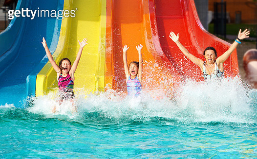 Girls who slipped on the slide, and when they fall into the water they have raised hands and eyes closed with emotion and enthusiasm - gettyimageskorea