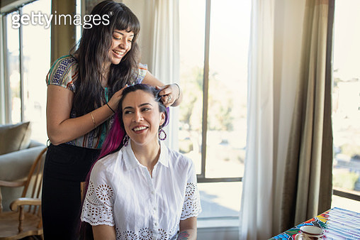 Millennial Latina Girlfriends Getting Ready for a Party, One is Braiding the Other's Hair, Both Smiling, Indoors - gettyimageskorea