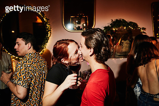 Laughing couple kissing while on date in night club - gettyimageskorea