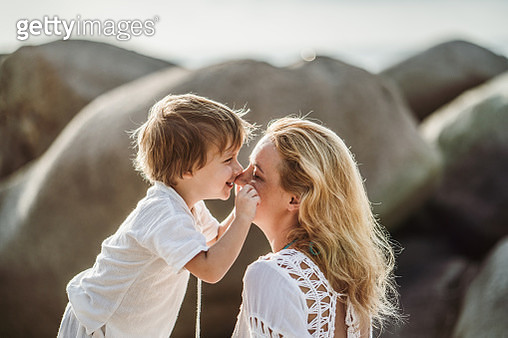 Cute boy showing affection towards his mother while pinching her for cheeks in summer day. - gettyimageskorea