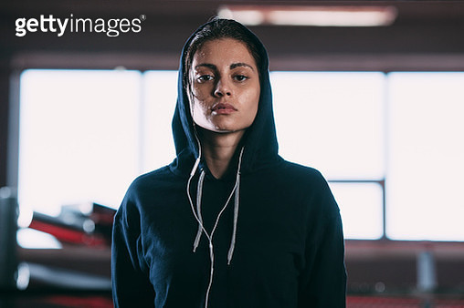 Portrait of tired woman wearing hooded shirt standing at gym - gettyimageskorea