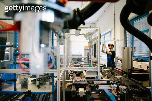industry 4.0: Young engineer works with a head-mounted display and place a virtual robotic arm into the production line - gettyimageskorea