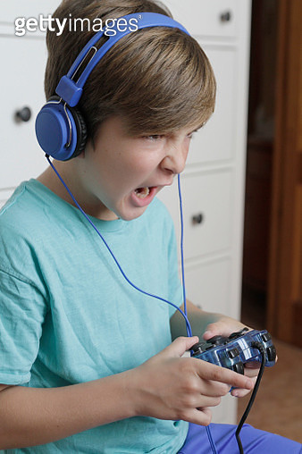 Excited boy playing video game at home - gettyimageskorea