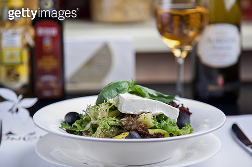 Fresh salad with feta and herbs served in a restaurant table with a glass of white wine - gettyimageskorea